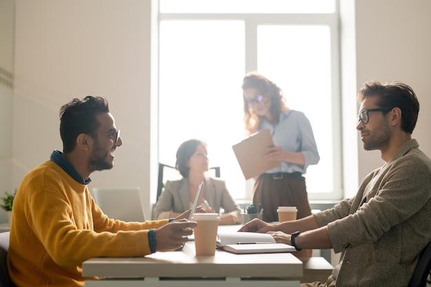 Pozytywni młodzi eksperci ds. marketingu wieloetnicznego siedzą przy stole w sali konferencyjnej i dzielą się pomysłami podczas omawiania nowej kampanii reklamowej