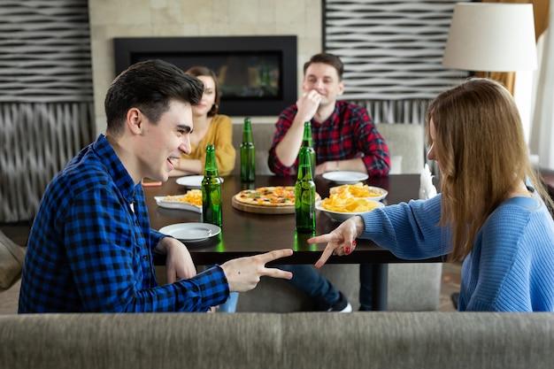 Pozytywni młodzi ludzie śmieją się grając w papier nożycowy kamień w barze