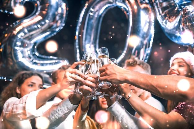 Pozytywni młodzi ludzie trzymają balony z nowym 202 rokiem i świętują.