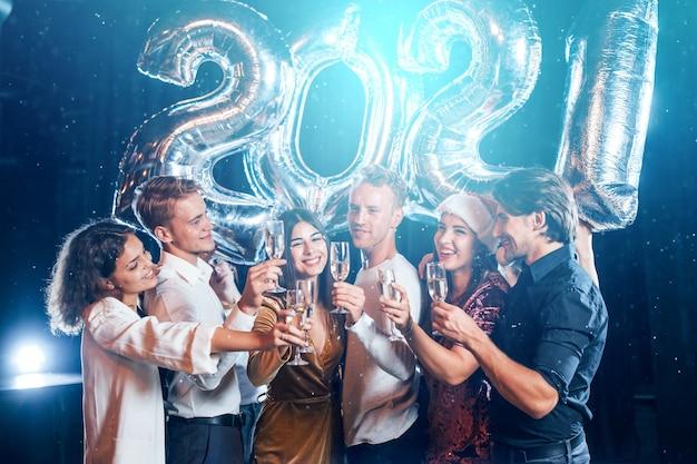 Pozytywni młodzi ludzie trzymają balony z nowym rokiem 2021 i świętują.
