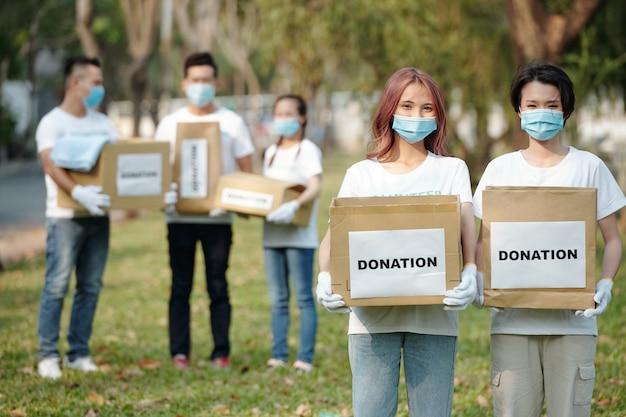 Pozytywni młodzi wolontariusze z azji w maskach medycznych trzymający kartonowe pudełka z jedzeniem i ubraniami dla osób, które straciły pracę z powodu pandemii koronawirusa