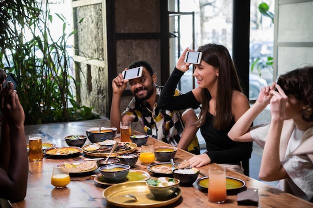 Pozytywni nastoletni przyjaciele siedzący przy kawiarni i grający w zgadywanie słów za pomocą smartfonów