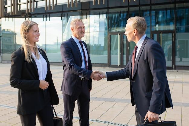 Pozytywni partnerzy biznesowi spotykają się w biurowcu, ściskają sobie ręce. widok z boku, średni strzał. koncepcja komunikacji korporacyjnej lub uścisk dłoni