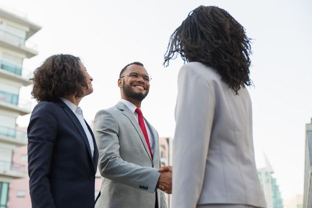 Pozytywni partnerzy biznesowi spotykający się na zewnątrz
