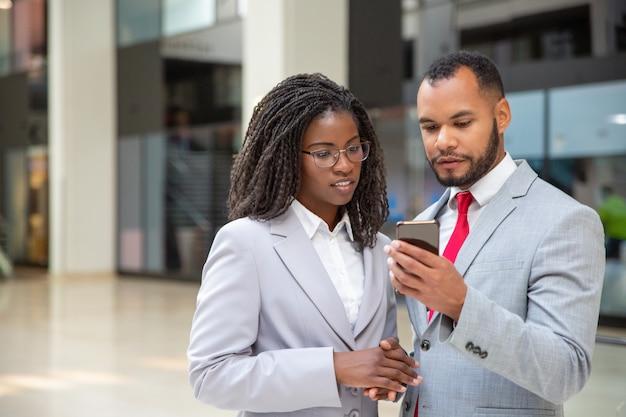 Pozytywni skupiający się koledzy patrzeje ekran telefonu komórkowego