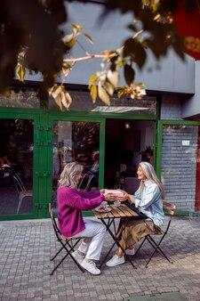 Pozytywni starsi towarzysze kobiet trzymają pudełko upominkowe siedzący stół na tarasie kawiarni