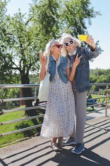 Pozytywni turyści. radosne starsze osoby cieszą się ze wspólnego spaceru podczas podróży