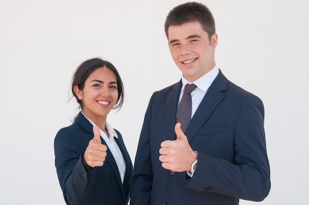 Pozytywni ufni biznesowi koledzy pokazuje aprobaty