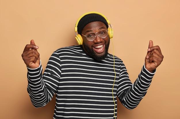 Pozytywnie beztroski mężczyzna podnosi ramiona, tańczy w rytm melodii, słucha fajnej muzyki przez słuchawki, ubrany niedbale