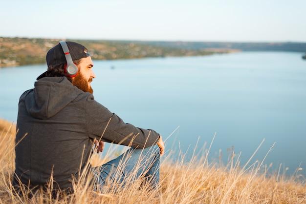 Pozytywnie brodaty mężczyzna siedzi na boisku, słuchając muzyki i odwracając wzrok w pobliżu rzeki