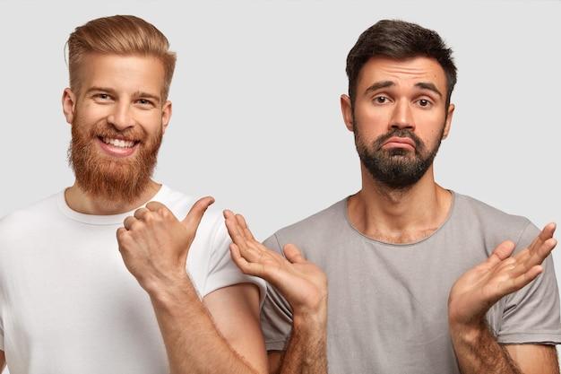 Pozytywnie brodaty młody rudowłosy mężczyzna z zadowolonym wyrazem twarzy wskazuje kciukiem na swojego zdziwionego przyjaciela, który ściska ręce i nie może podjąć decyzji, co robić, odizolowany na białej ścianie