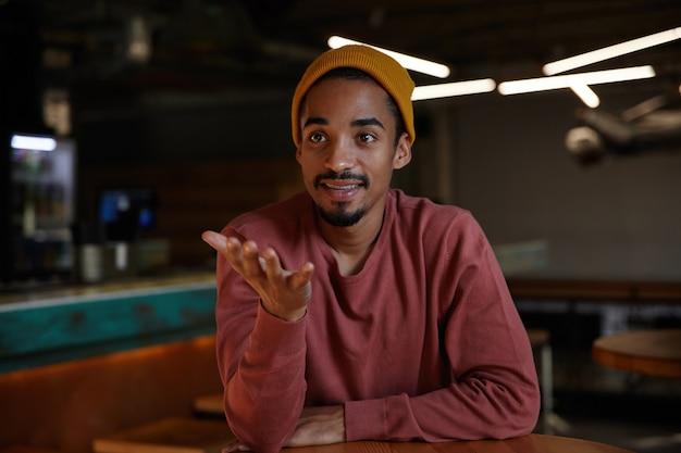 Pozytywnie dobrze wyglądający, ładny brodaty ciemnoskóry mężczyzna pozuje nad wnętrzem kawiarni w zwykłych ubraniach, patrząc na bok ze spokojną twarzą i emocjonalnie podnosząc dłoń