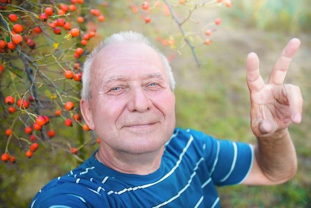 Pozytywnie emerytowany dziadek, robi selfie w parku ze smartfonem