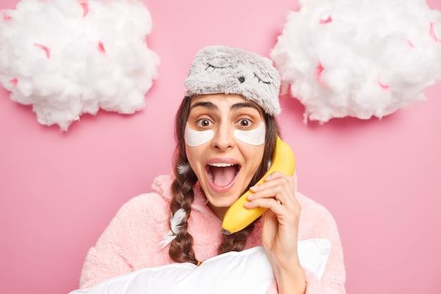 Pozytywnie emocjonalna kobieta o ciemnych włosach trzyma otwarte usta, nakłada kolagenowe plastry pod oczy