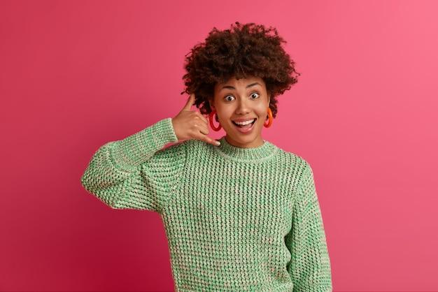 """Pozytywnie gadatliwa kobieta rasy mieszanej wykonuje gest """"zadzwoń do mnie"""", utrzymuje kontakt z przyjaciółmi w celu samoizolacji przez telefon, uśmiecha się przyjemnie, pozuje dobrze ubrana w domu, próbuje uzyskać czyjś numer"""