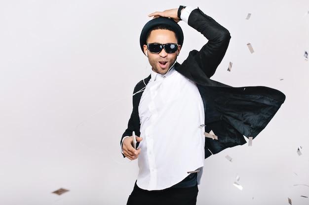 Pozytywnie podekscytowany przystojny facet w garniturze, kapeluszu, czarnych okularach przeciwsłonecznych, zabawy. słuchanie muzyki przez słuchawki, taniec, śpiew, świętowanie, szczęście.