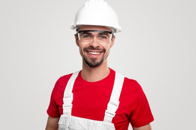 Pozytywnie przyjazny brodaty pracownik płci męskiej w ogólnym i ochronnym kasku i okularach uśmiechający się i patrzący na kamerę na białym tle