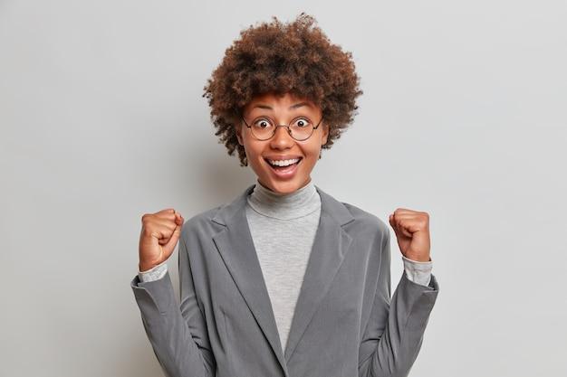Pozytywnie triumfująca bizneswoman zaciska pięści świętuje udaną transakcję otrzymuje promocję ubrana w elegancki szary formalny garnitur nosi okrągłe okulary pozuje w pomieszczeniach