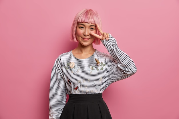 Pozytywnie uśmiechnięta różowowłosa dziewczyna pokazuje znak pokoju, nosi sweter w paski i czarną spódnicę