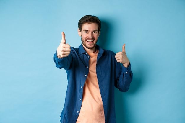 Pozytywnie uśmiechnięty facet pokazujący kciuki do góry i uśmiechnięty, komplementujący, chwalący dobrą robotę, dobrze wykonany gest, stojący na niebieskim tle.