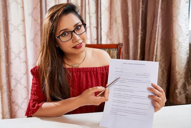 Pozytywnie uśmiechnięty młody agent nieruchomości wyjaśniający, jak wypełnić dane osobowe w formularzu umowy najmu