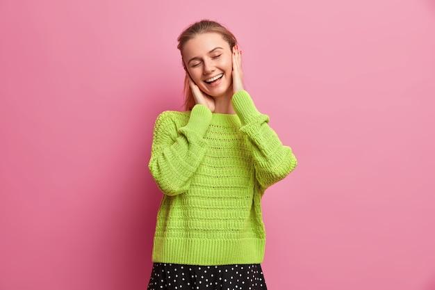 Pozytywnie uszczęśliwiona młoda europejka, uśmiecha się szeroko, dobrze się bawi w domu
