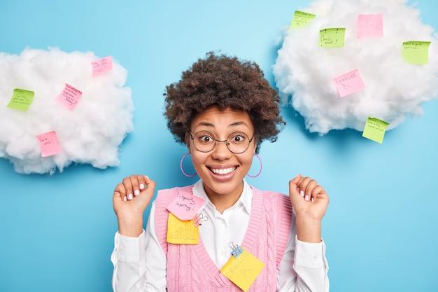 Pozytywnie wesoła afroamerykanka podnosi rękę i patrzy podekscytowana z przodu, zadowolona, że słyszy pochwałę za dobrą pracę nosi okrągłe okulary formalne ubranie otoczone karteczkami z zadaniami pisemnymi