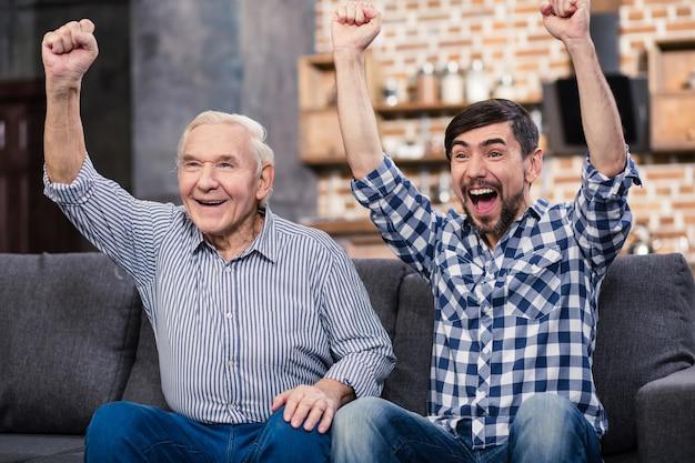 Pozytywnie wiekowy ojciec i syn oglądający piłkę nożną w domu