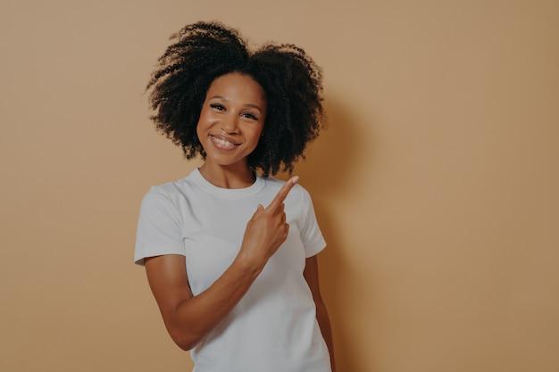 Pozytywnie wyglądająca afrykańska modelka w białej koszuli wskazująca palcem wskazującym na pustą przestrzeń i uśmiechnięta, wskazująca na prawy górny róg. koncepcja reklamy i promocji