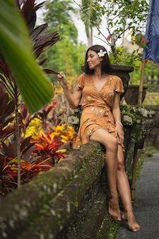 Pozytywnie zachwycona kobieta siedząca na podporze i dotykająca egzotycznych liści podczas sesji zdjęciowej