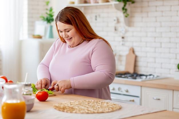 Pozytywnie zachwycona kobieta stojąca w kuchni podczas krojenia sałaty na sałatkę