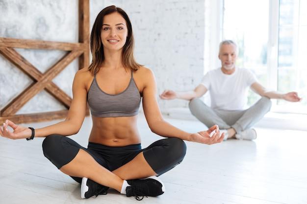 Pozytywnie zachwycona suczka siedząca ze skrzyżowanymi nogami na podłodze i uśmiechnięta na twarzy patrząc do przodu