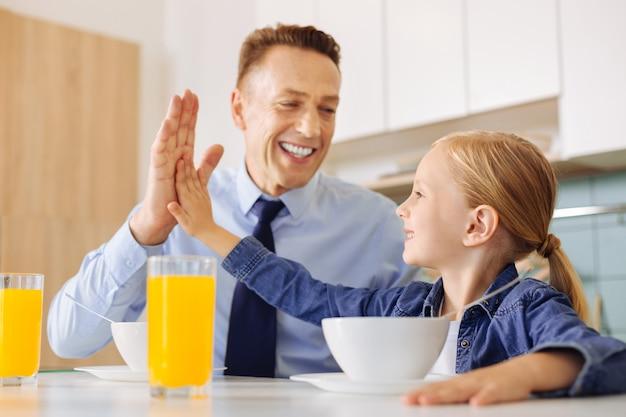 Pozytywnie zachwycona sympatyczna dziewczyna siedząca przy stole i patrząc na swojego ojca przybijając mu piątkę
