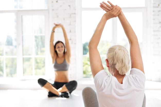 Pozytywnie zachwycona trenerka jogi siedzi naprzeciw koleżanki krzyżującej nogi, unosząc obie ręce nad głowę