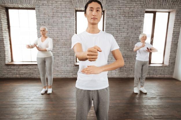 Pozytywnie zachwycony ciemnowłosy mężczyzna ubrany w białą koszulkę trzymający lewą rękę zgiętą w łokciu, robiąc pięść na prawej ręce
