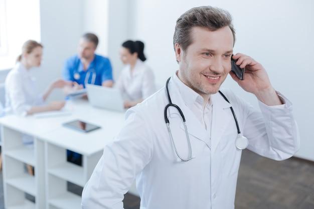 Pozytywnie zachwycony doświadczony lekarz pracujący w klinice i cieszący się rozmową telefoniczną, podczas gdy koledzy cieszą się rozmową za plecami