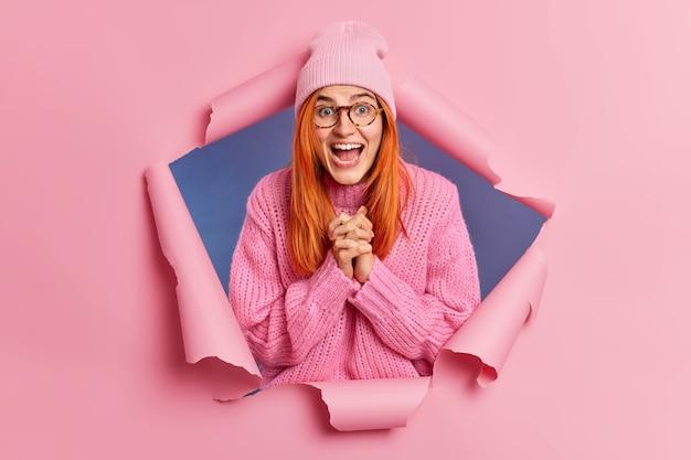 Pozytywnie zaskoczona rudowłosa piegowata kobieta reaguje na coś niesamowitego, splata dłonie i otwiera usta ze zdumieniem, czuje się szczęśliwa ubrana w luźne różowe ciuchy, nosi okulary.