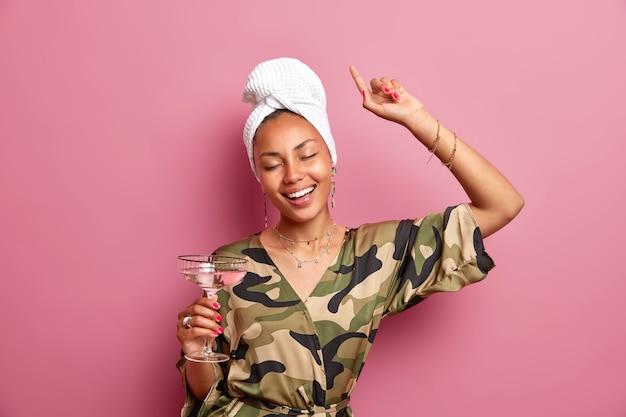 Pozytywnie zrelaksowana etniczna kobieta o ciemnej skórze ma zamknięte oczy podnosi ramiona przy koktajlu w domu bawi się na domowej imprezie nosi szlafrok w kolorze khaki biały ręcznik owinięty na głowie modelki w pomieszczeniach