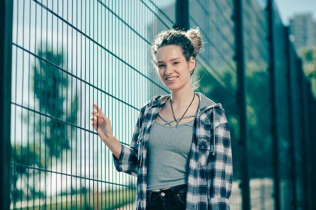 Pozytywnie zrelaksowana młoda kobieta ubrana w zwykłe ubrania i uśmiechnięta stojąc w pobliżu ogrodzenia z ogniw łańcucha
