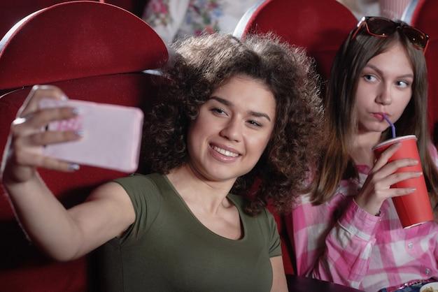 Pozytywność atrakcyjna brunetka z kręconymi włosami trzymająca różowego smartfona i robiąca selfie. ładna dziewczyna oglądając śmieszne ciekawe komedie z uśmiechem