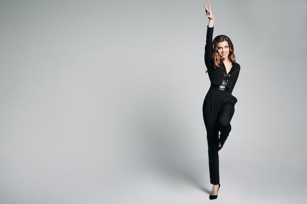 Pozytywności dziewczyna w czarnym apartamencie skacze w studiu z wzrostem up.