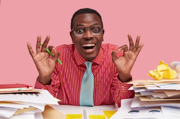 Pozytywny afro amerykanin robi gest obiema rękami, szeroko się uśmiecha, demonstruje, że wszystko w porządku, ubrany w formalne ubranie, trzyma długopis