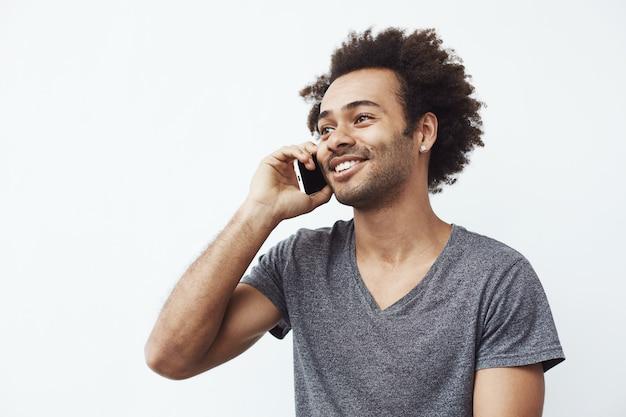Pozytywny afrykański mężczyzna ono uśmiecha się opowiadający na telefonie.