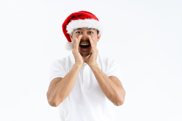 Pozytywny azjatycki mężczyzna cupping ręki wokoło usta i krzyczeć głośno