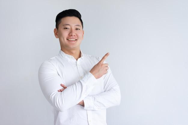 Pozytywny azjatycki mężczyzna wskazuje palec na boku