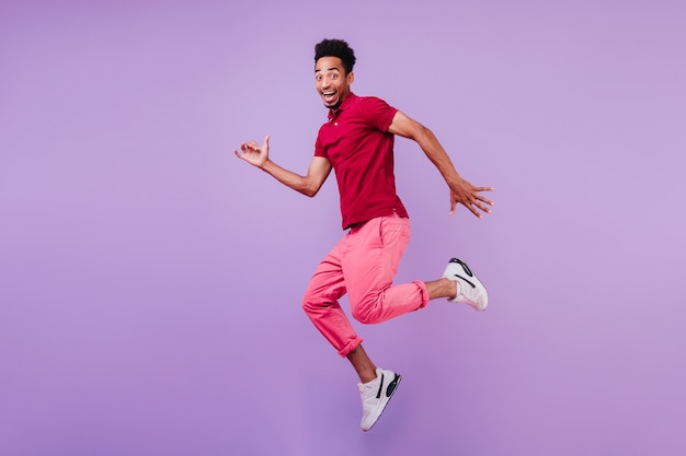 Pozytywny beztroski afrykański mężczyzna w butach sportowych, taniec. przystojny zadowolony facet w różowe spodnie skacze z uśmiechem.