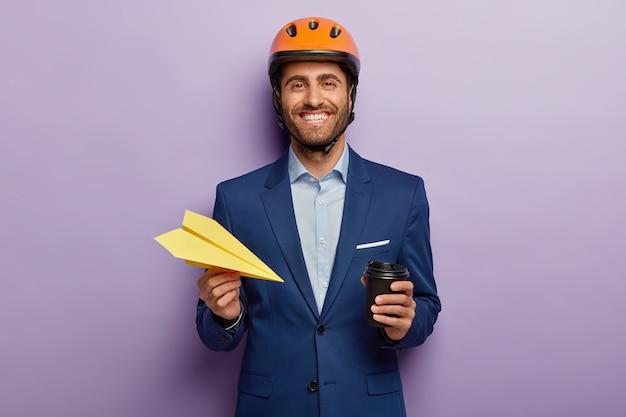 Pozytywny biznesmen pozuje w eleganckim garniturze i czerwonym kasku w biurze