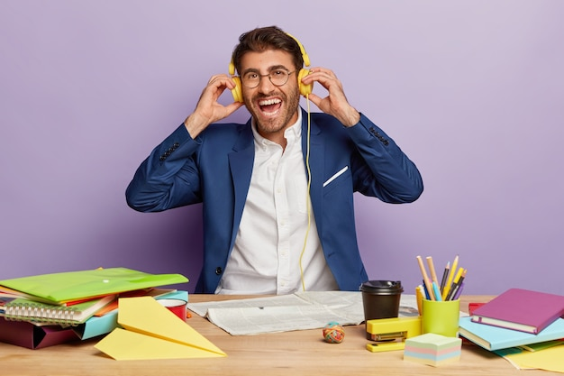 Pozytywny biznesmen siedział przy biurku