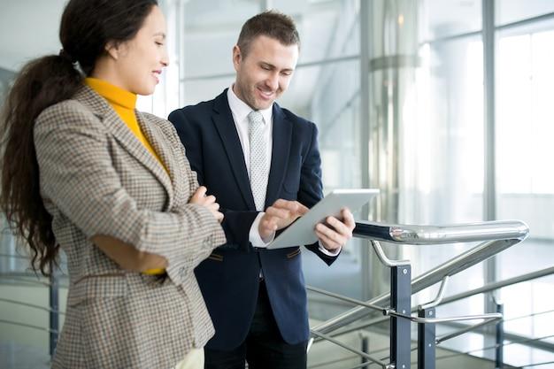 Pozytywny biznesmen z asystentem używa pastylkę