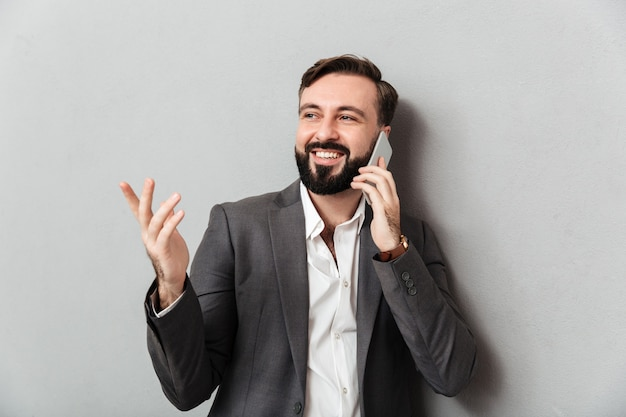 Pozytywny biznesowy facet w formalnej odzieży mobilnym gawędzeniu gestykuluje podczas gdy używać telefon komórkowego, odizolowywającego nad popielatym